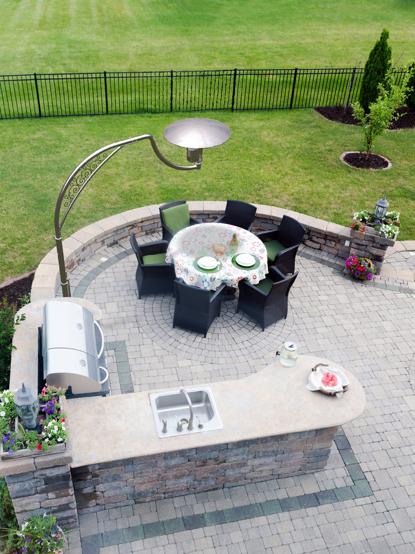Aerial view of outdoor heater positioned directly above a round table & 6 black chairs. Location is at a residential garden patio which includes a BBQ system, a wash basin on a granite countertop & some pretty flowers.